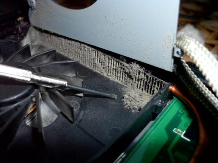 Приподнимаем крышку на гибкой перемычке и аккуратно очищаем ребра радиатора тонкой отверткой