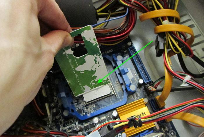 С помощью пластиковой карточки аккуратно разравниваем вещество по всей плоскости процессора