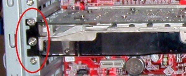 Откручиваем винт, крепящий видеокарту к корпусу компьютера и аккуратно вытягиваем видеокарту